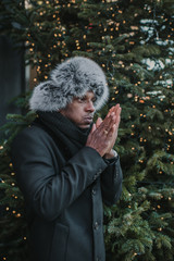 Black man warming hands near Christmas tree on street