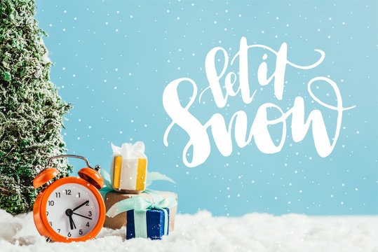 """close-up shot of christmas gifts with alarm clock and miniature christmas tree standing on snow on blue background with """"let it snow"""" lettering"""