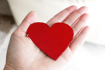 A red symbolic heart of a cardboard hold laying on a hand