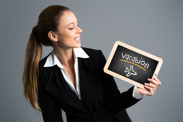 "young businesswoman hold blackboard with message ""vacation"""