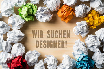"""Nachricht """"Wir suchen Designer"""" auf Holzuntergrund, umrandet von vielen zerknüllten Papierkugeln"""