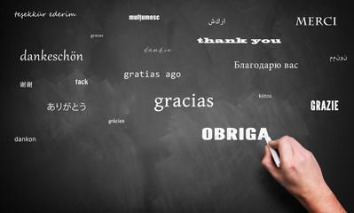 """Hand schreibt das Wort """"Danke"""" in vielen Sprachen auf Kreidetafel"""