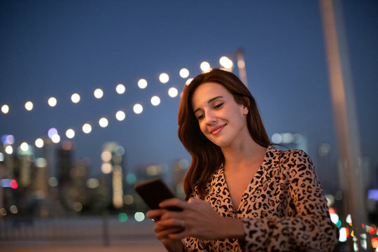 Young adult female looking at smartphone on a rooftop party at night