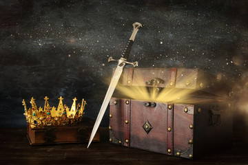 low key image of beautiful queen/king crown over antique old book, open chest with treasure and sword. fantasy medieval period.