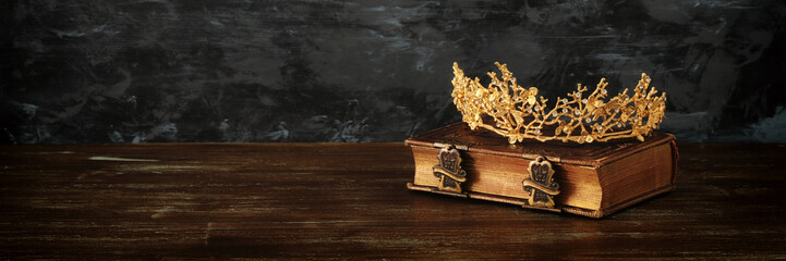 low key image of beautiful queen crown on old book. fantasy medieval period.