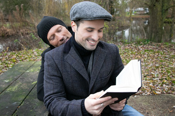 Male gay couple sit on ben in park to read to each other from book
