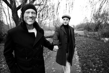 Black and white portrait of male gay couple holding hands and smiling as they walk through park
