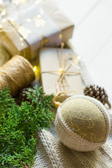 Christmas New Year presents packaging. Gift boxes in craft paper tied with twine hand made linen fabric ball white knitted sweater on wood table by window. Golden garland lights. Cozy winter evening
