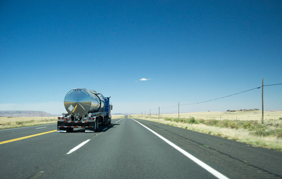 truck with a silver tank trailer passing a passenger car on a highway