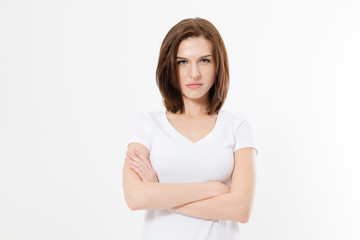Upset and angry girl in white blank t shirt isolated on white background. Sad and mad woman with crossed arms . Copy space.