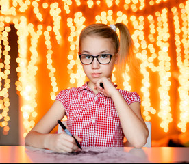 Blonde girl in the pink dress and big black glasses drawing santa claus. Christmas and New Year theme, yellow bokeh