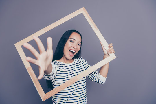 Close-up portrait of nice attractive funny cheerful cheery straight-haired lady in striped pullover holding frame hand going through isolated on gray pastel background