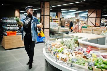 Stylish casual african american man at jeans jacket and black beret holding coconuts and pineapple in fruits organic section of supermarket.