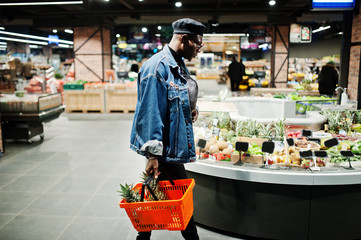 Stylish casual african american man at jeans jacket and black beret holding basket with pineapples in fruits organic section of supermarket.