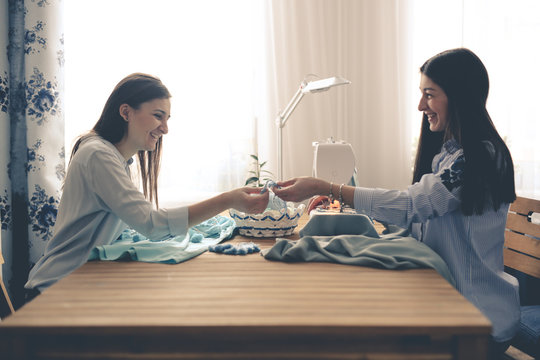 Two beautiful women sew together on sewing machine
