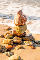 Zen stone pyramid at a beach with surf