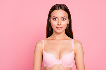 Close up portrait of cute gentle half bare nude her she girl wearing pale pink bra isolated on rose background