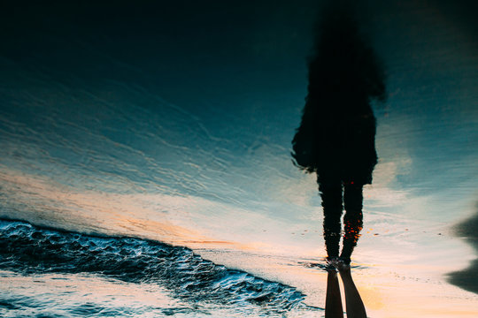 Reflection silhouette of a young woman at the seashore with sunset light