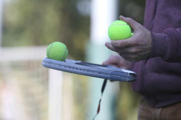 Tennis player holds Tennis balls on a racket
