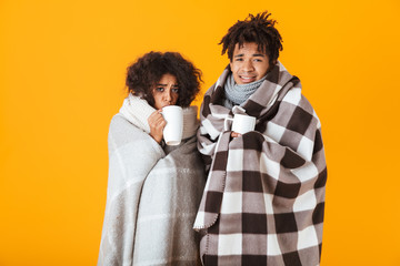 Frozen african couple wrapped in cozy blankets
