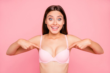 Close up portrait of attractive beautiful delighted gorgeous skinny her she girl showing nice proportions of decollete cleavage in push up bra isolated on pink background
