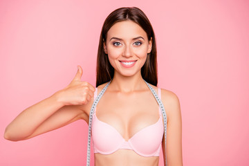 Portrait of nice sweet lovely adorable attractive winsome fascinating positive girl in beige bra tape cm showing thumbs-up ad advert advertising isolated over pink background