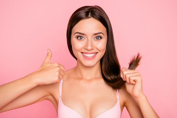 Close-up portrait of nice sweet lovely attractive positive optimistic cheerful girl in beige bra holding in hand shine strong silky straight hair curls showing thumbs-up isolated over pink background