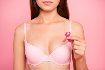Health medicine support charity concept. Cropped close-up portrait of attractive caucasian girl lady in beige bra holding in hand showing sign symbol small ribbon isolated over pink pastel background