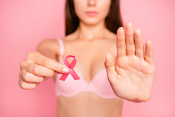 Medical problem trouble solving. Cropped close-up portrait of caucasian attractive girl in beige bra holding in hand showing sign symbol small ribbon restriction palm isolated over pink background