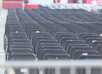 Rows of empty dark chairs. Abstract. Front view