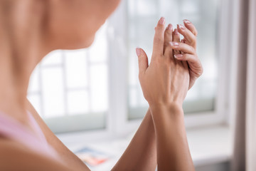 Beautiful woman with sensitive skin putting some cream on her hands
