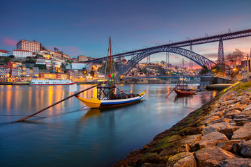 Porto, Portugal. Cityscape image of Porto, Portugal with reflection of the city in the Douro River and the Luis I Bridge during sunrise.