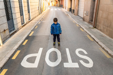 Little kid looking a stop signal of traffic on the ground