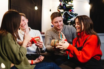 Christmas and New Year vibes. Home decorations. Charming young woman in red sweater sits on the couch before shiny Christmas tree and opens present boxes with her friends