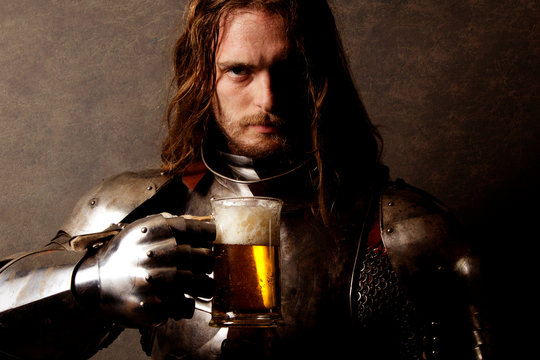 Portrait of a knight in armor drinking a beer