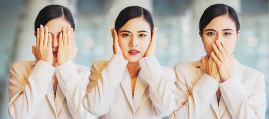 Woman covering eyes, ears and mouth with hands as looking like the three wise monkeys. Don't see, don't hear and don't speak concept