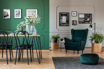 Elegant bottle green dining room with wooden table with black chairs and emerald green armchair and pouf