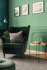 Grey pillow on emerald green armchair in green living room interior with posters on the wall and wooden coffee table