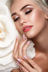 Beautiful tender girl with natural make up and designer manicures with flowers. Beauty face.