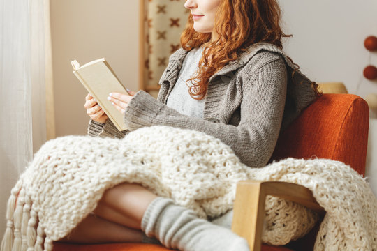 Woman with blanket on knees sitting on armchair and reading book