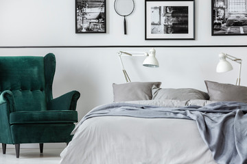 Photo collector bedroom with emerald armchair and king size bed with grey bedding