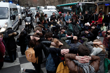 Students and high school students kneel with hands over their head in a street during a demonstration to protest against the French government's reform plan, in Paris