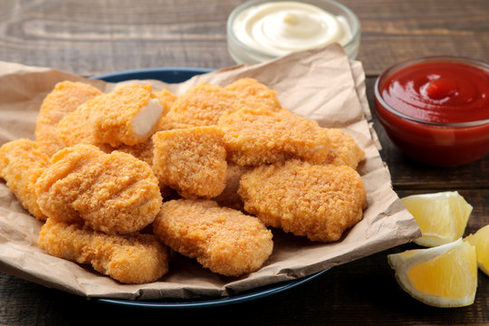 chicken nuggets with red and white sauce on a brown wooden background. fast food close-up