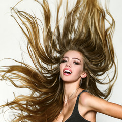 Perfect long hair. Blonde wave long hair. Perfect girl smiling on white background. Beauty and perfect health hair. Beauty model with perfect clean skin. Long hair.