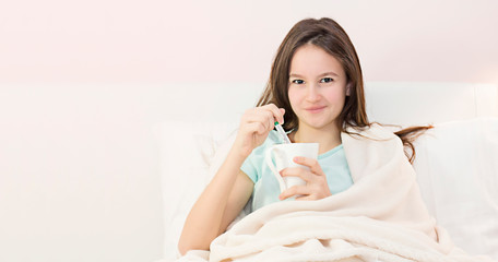 Teen girl lying in bed with a high fever