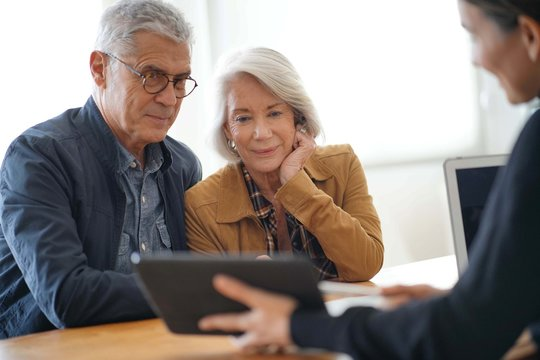 Modern senior couple going through remodelling ideas on tablet