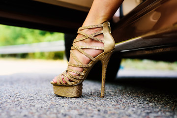 Womans legs in high heels. Luxury urban background. The woman is wearing shoes on high heels. Close up of woman legs. Woman legs in high heel golden shoes heels.