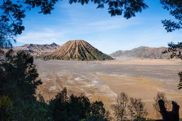 Mount Bromo volcano crater erupts in the caldera, behind Gunung Batok, with Gunung Semeru in the background, Java, Indonesia.