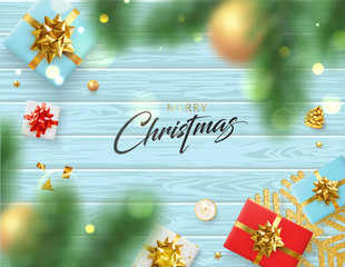 Merry Christmas card with gifts and blurred fir branches on wooden backdrop.