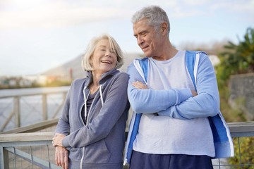 Healthy senior couple smiling at eachother outdoors